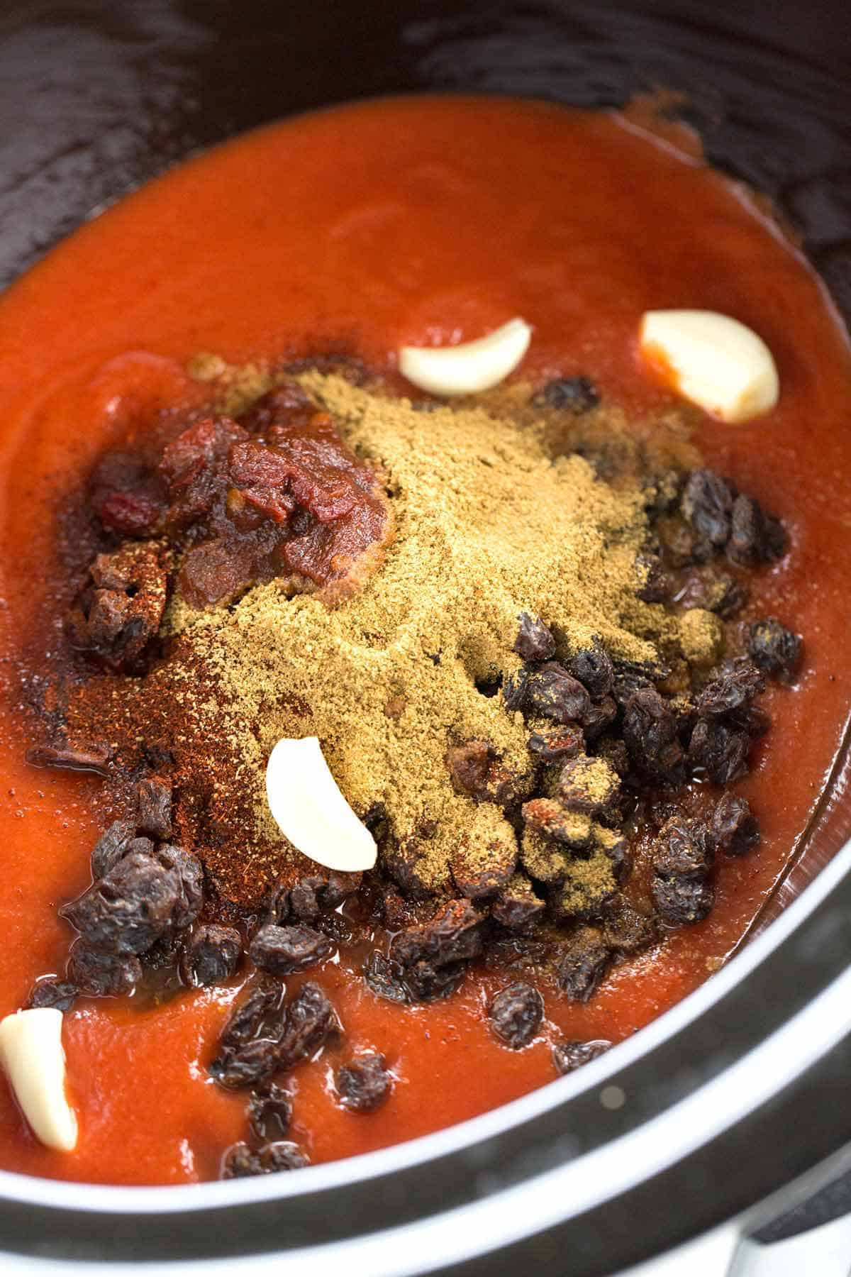 Adding the Mexican-style mole sauce ingredients into a slow cooker