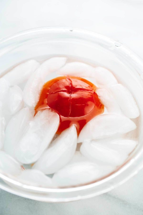 Tomato being shocked in a water with ice cubes