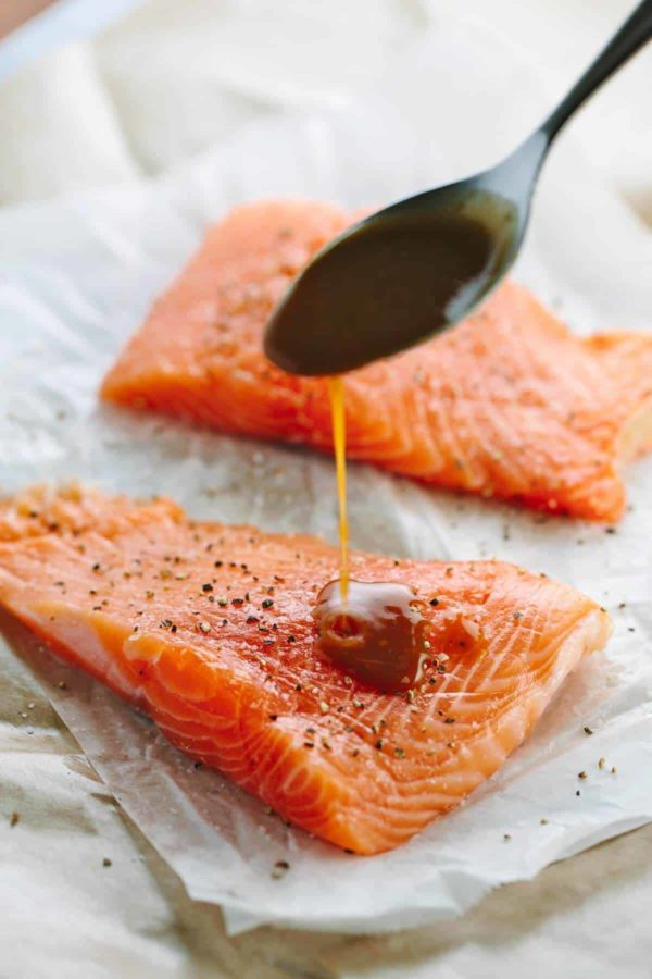 Pouring a miso and soy glaze over raw salmon fillets before cooking