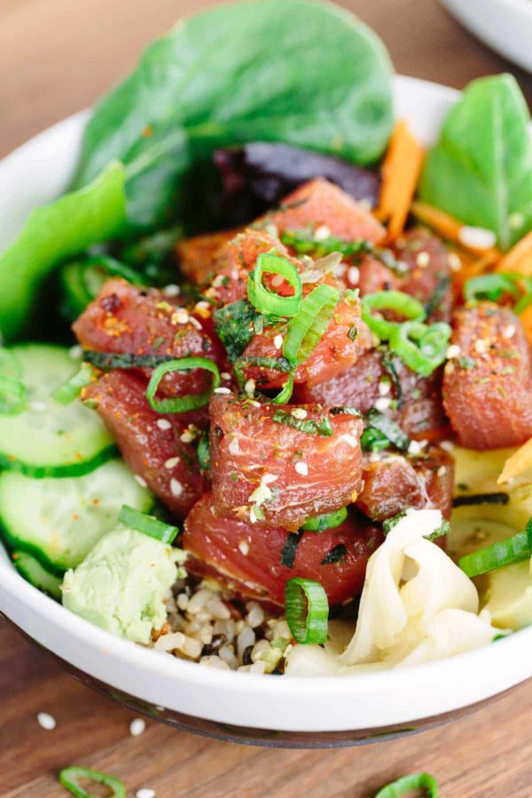 poke bowl with brown rice and sliced cucumbers