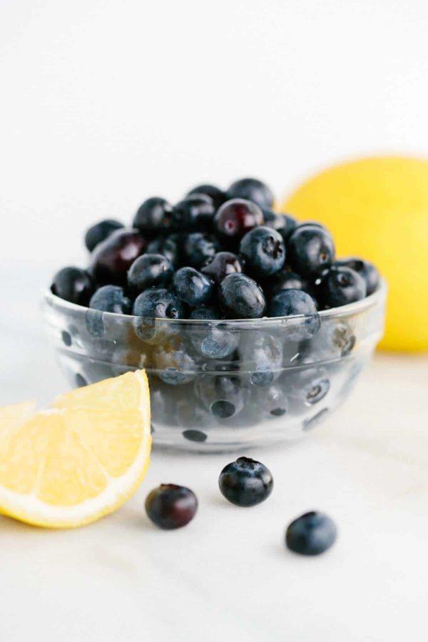 bowl of blueberries next to sliced lemon wedges