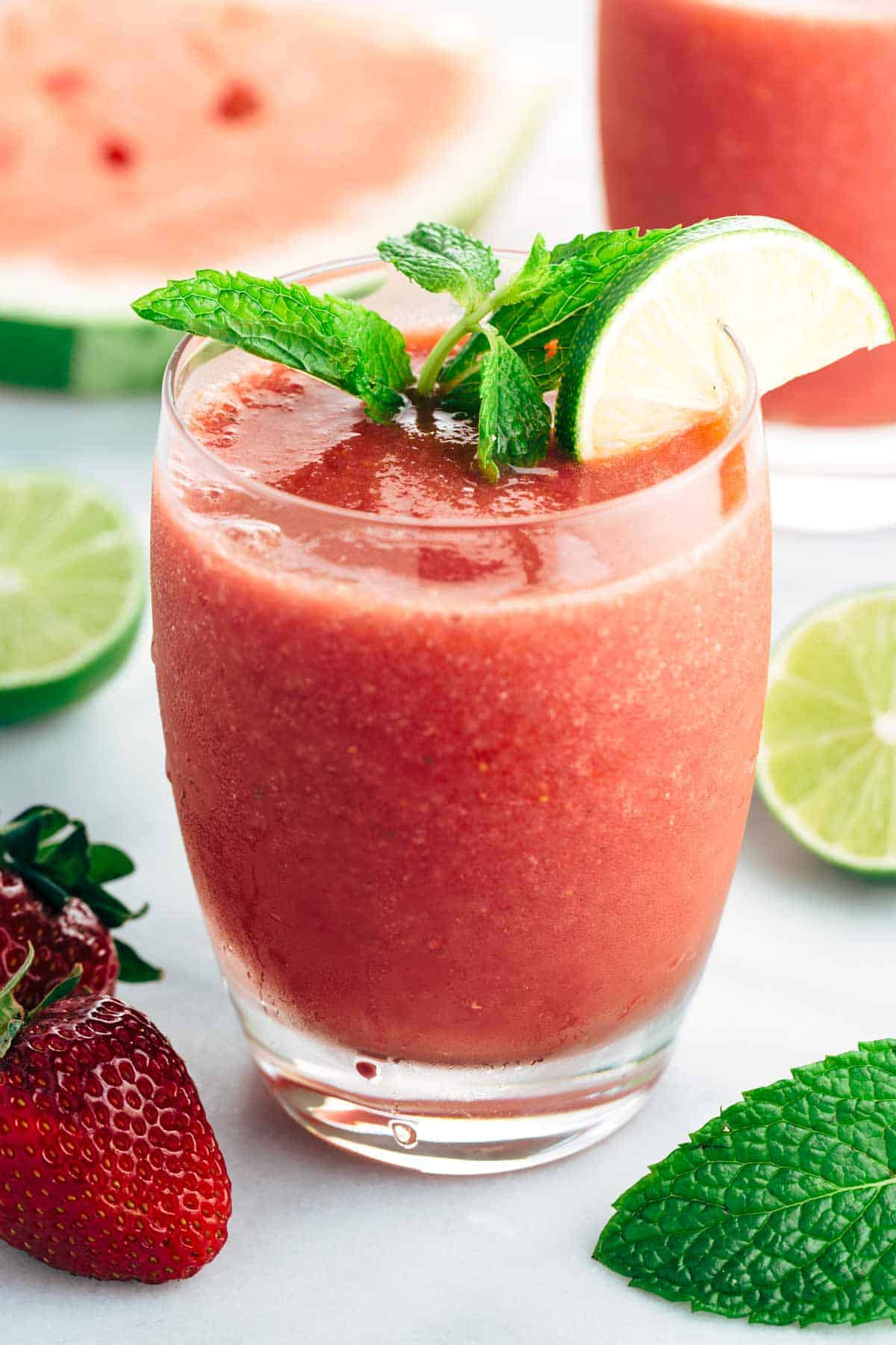 Glass of strawberry watermelon smoothie with mint and lemon