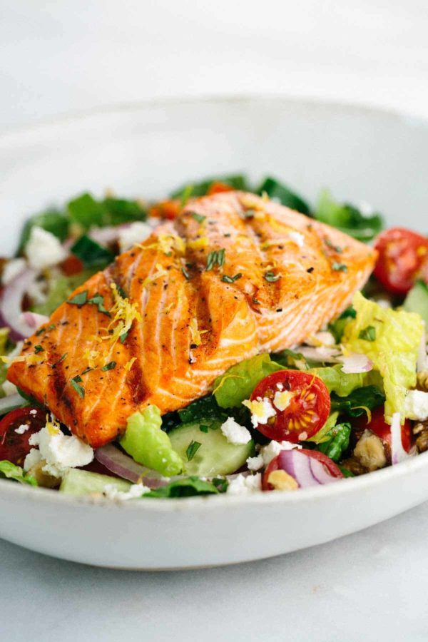 bowl of greek salad with a grilled piece of salmon on top