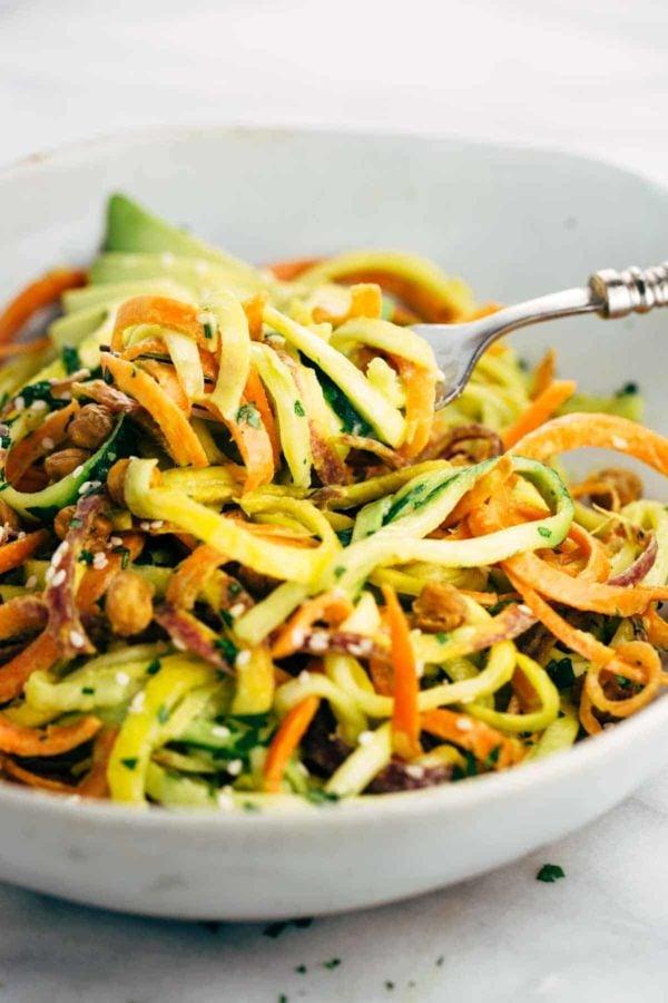 Fork twirling vegetable noodles out of a salad bowl