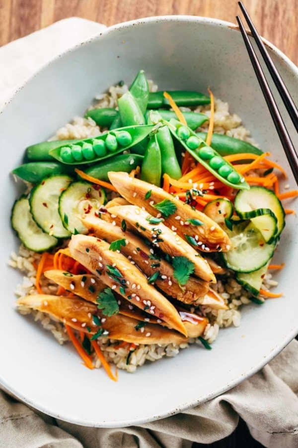 Bowl of sliced sesame chicken with snap peas and cucumbers