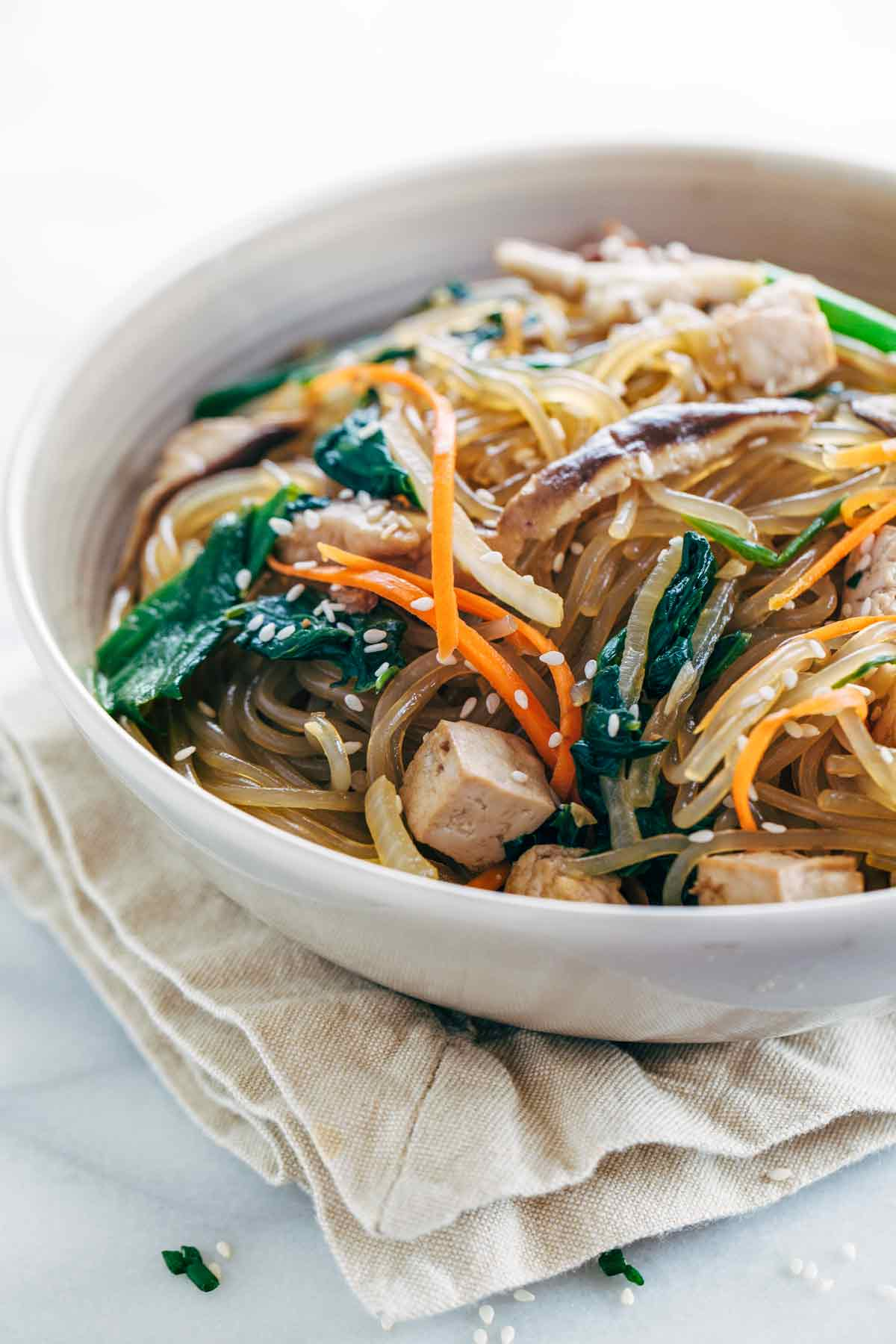 Bowl of Japchae Korean noodles with cubes of tofu and slices of mushrooms