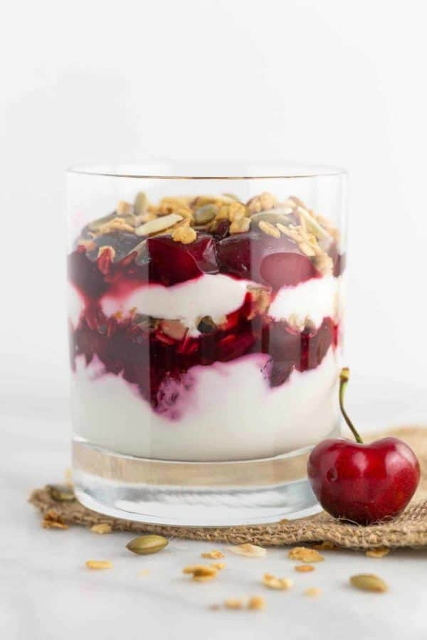 side view of a glass of cherry yogurt parfaits with granola