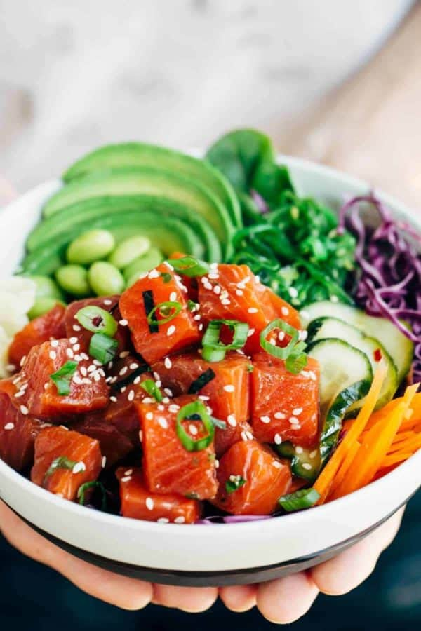 Hands holding a poke bowl with salmon and vegetables