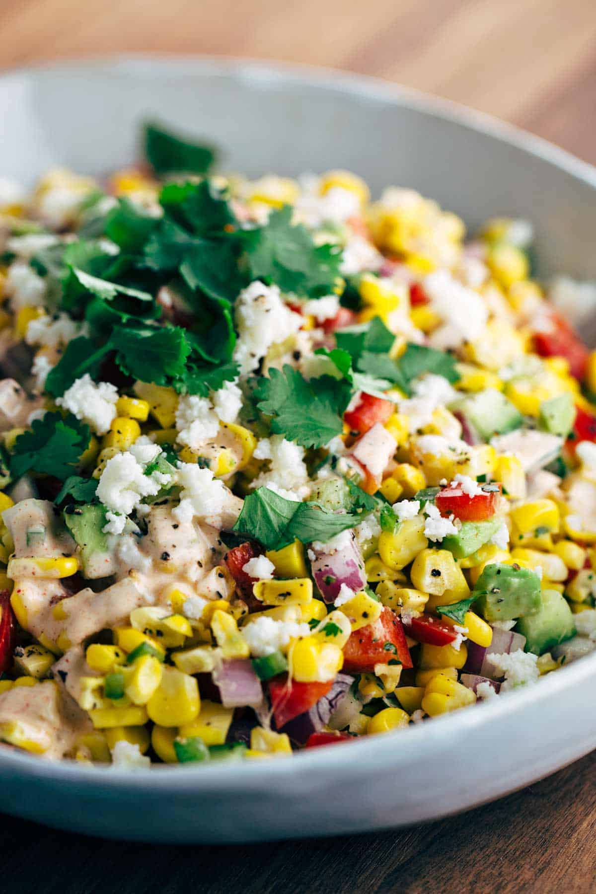 A bowl of corn salad with chipotle dressing and garnish