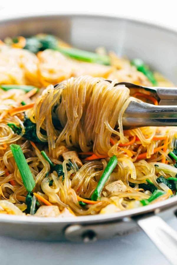 Metal tongs grabbing noodles from a saute pan