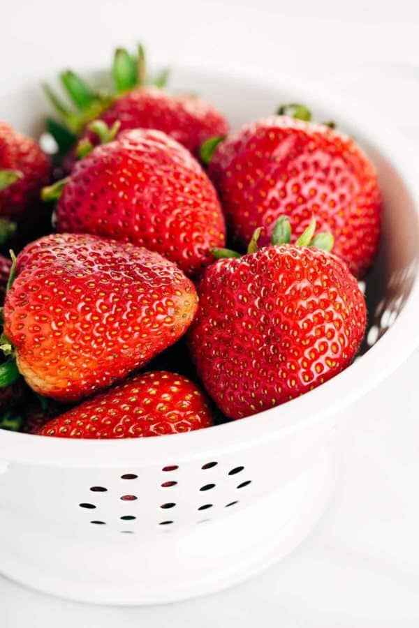 white colander filled with strawberries