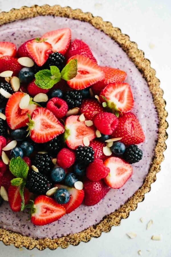 close up yogurt tart with fresh sliced strawberries and blueberries