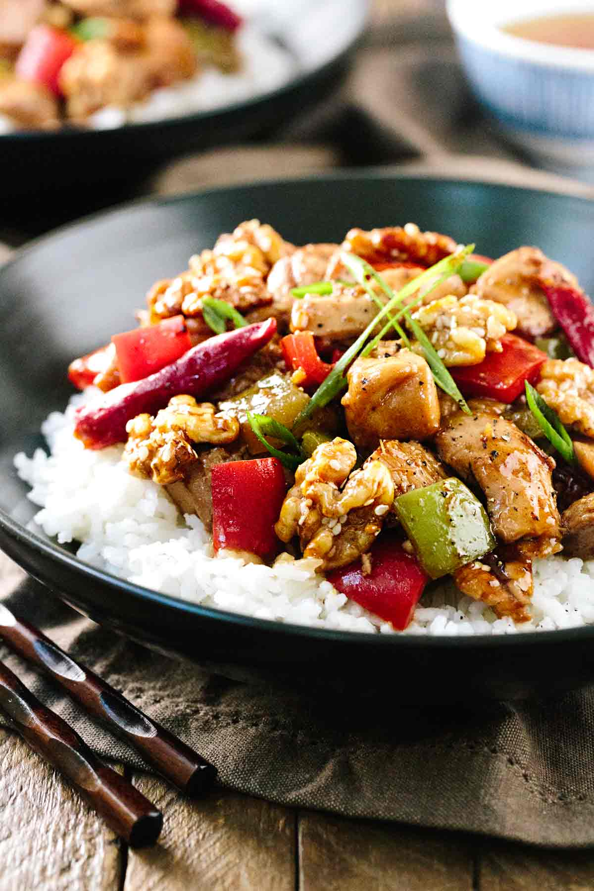 Black plate of Kung Pao Chicken over a bed of white rice