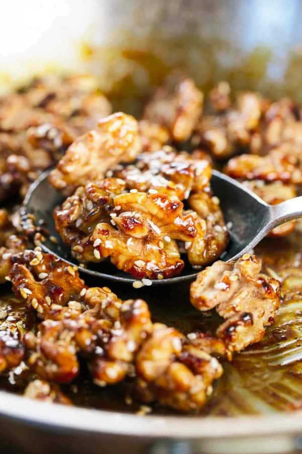Honey glazed walnuts cooking in a pan