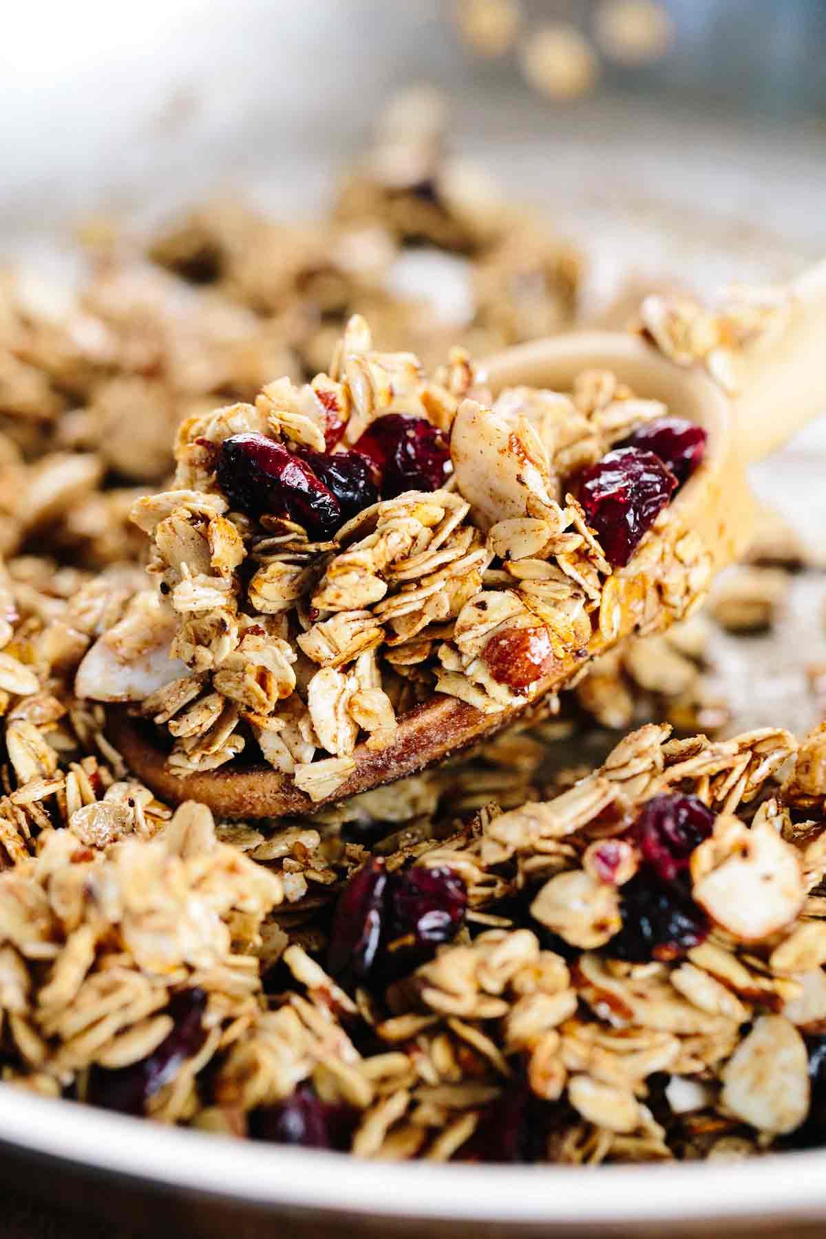Wooden spoon scooping granola