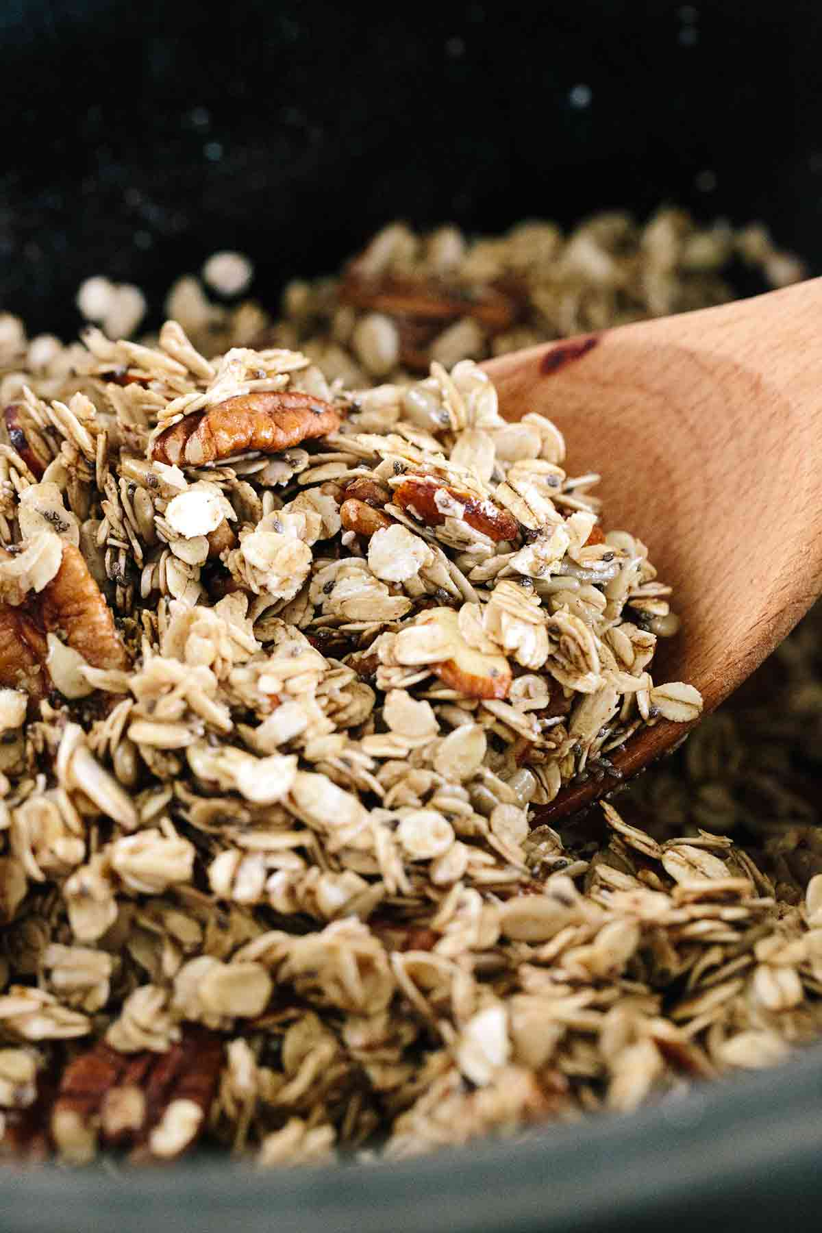 Wooden spoon mixing granola in a slow cooker
