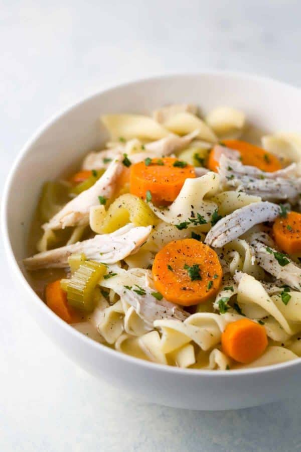 white bowl filled with chicken noodles soup with slices of carrots on top