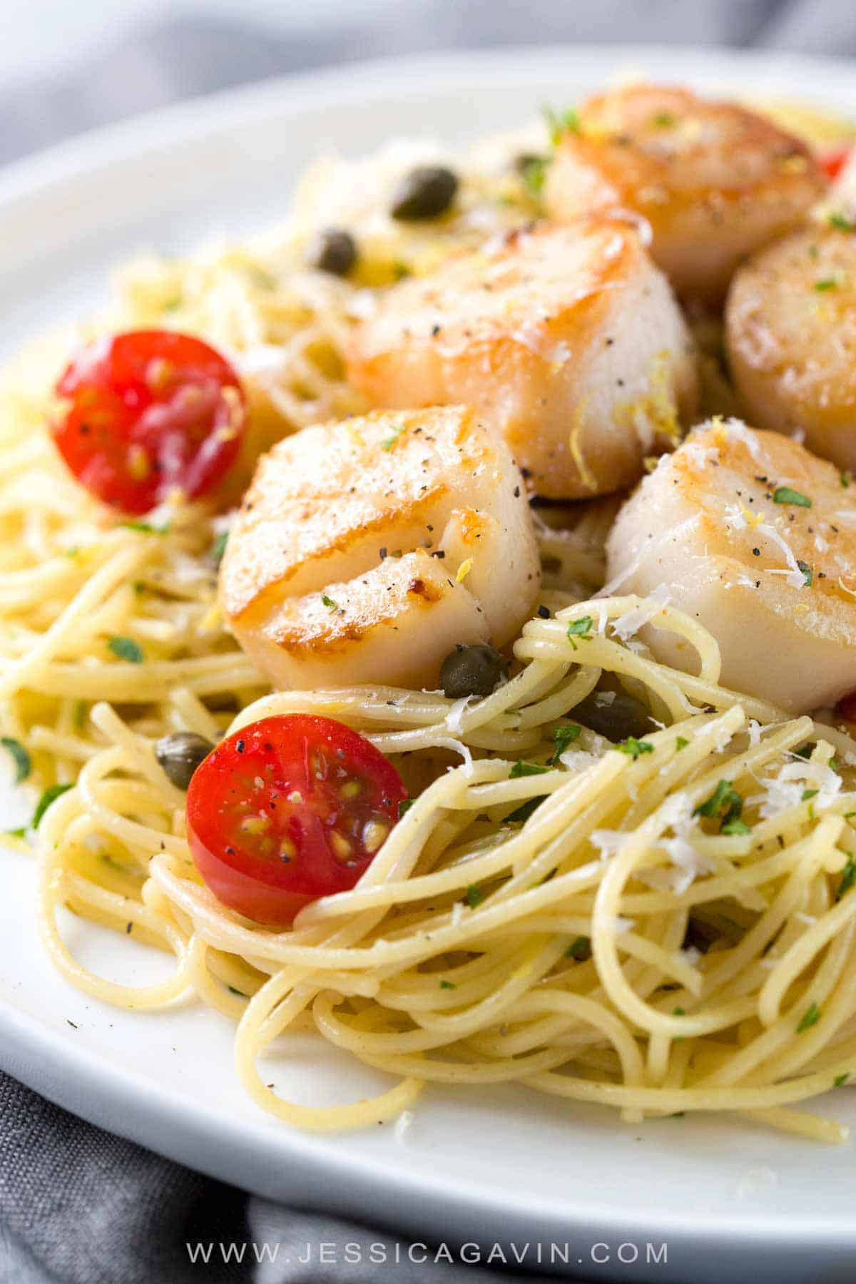 Pan Seared Scallops with Lemon Caper Pasta - Easy gourmet recipe for light angel hair pasta tossed with a citrus white wine sauce and tomatoes. #scallops #lemoncaper #pasta #searedscallops