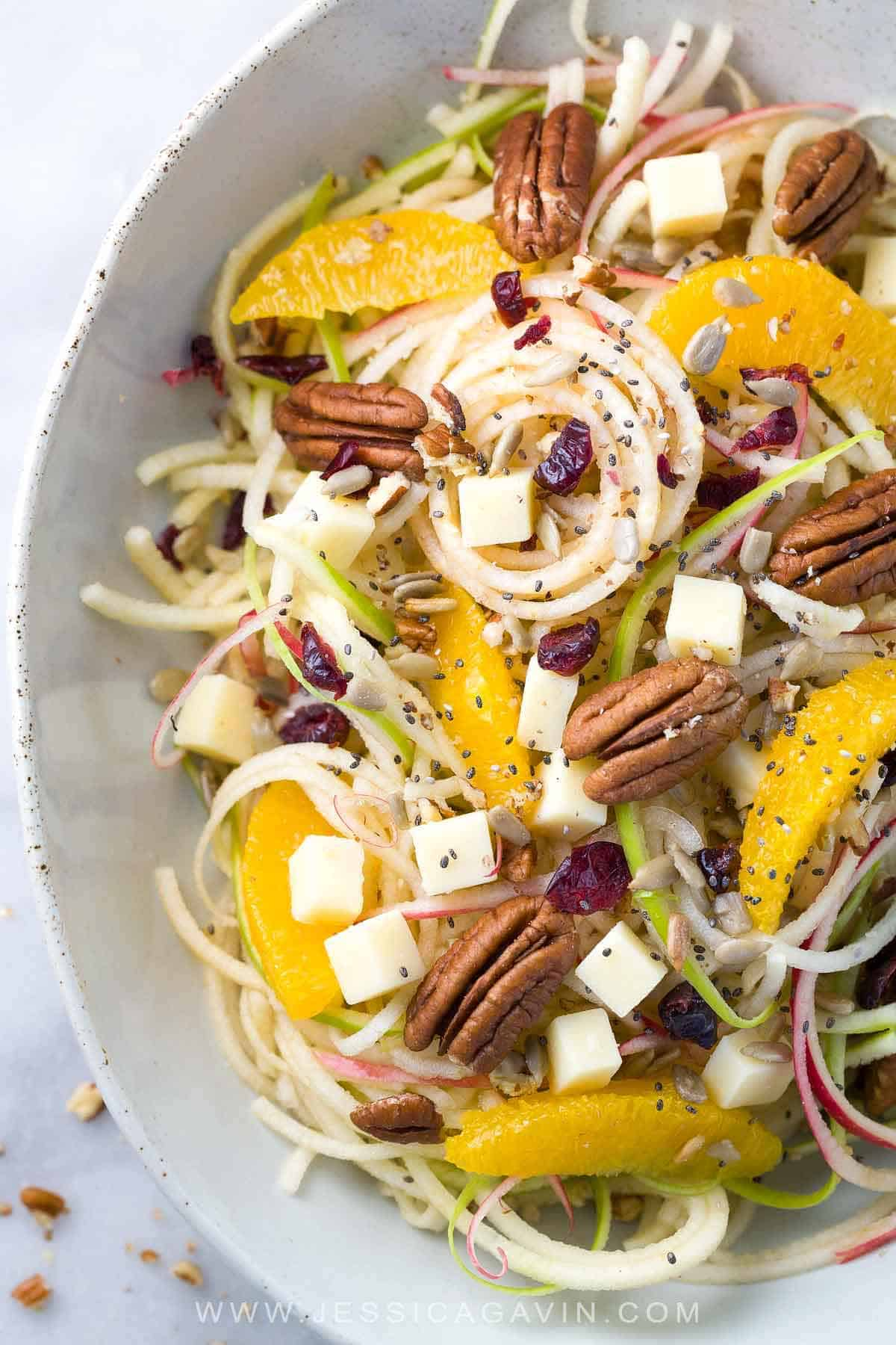 Spiralized Apple Salad with Citrus Dressing - Healthy and refreshing recipe made in only 15 minutes! Topped with oranges, pecans, cheddar cheese, cranberries, sunflower and chia seeds. #apples #salad #inspiralizer #spiralizedvegetables #healthyrecipes