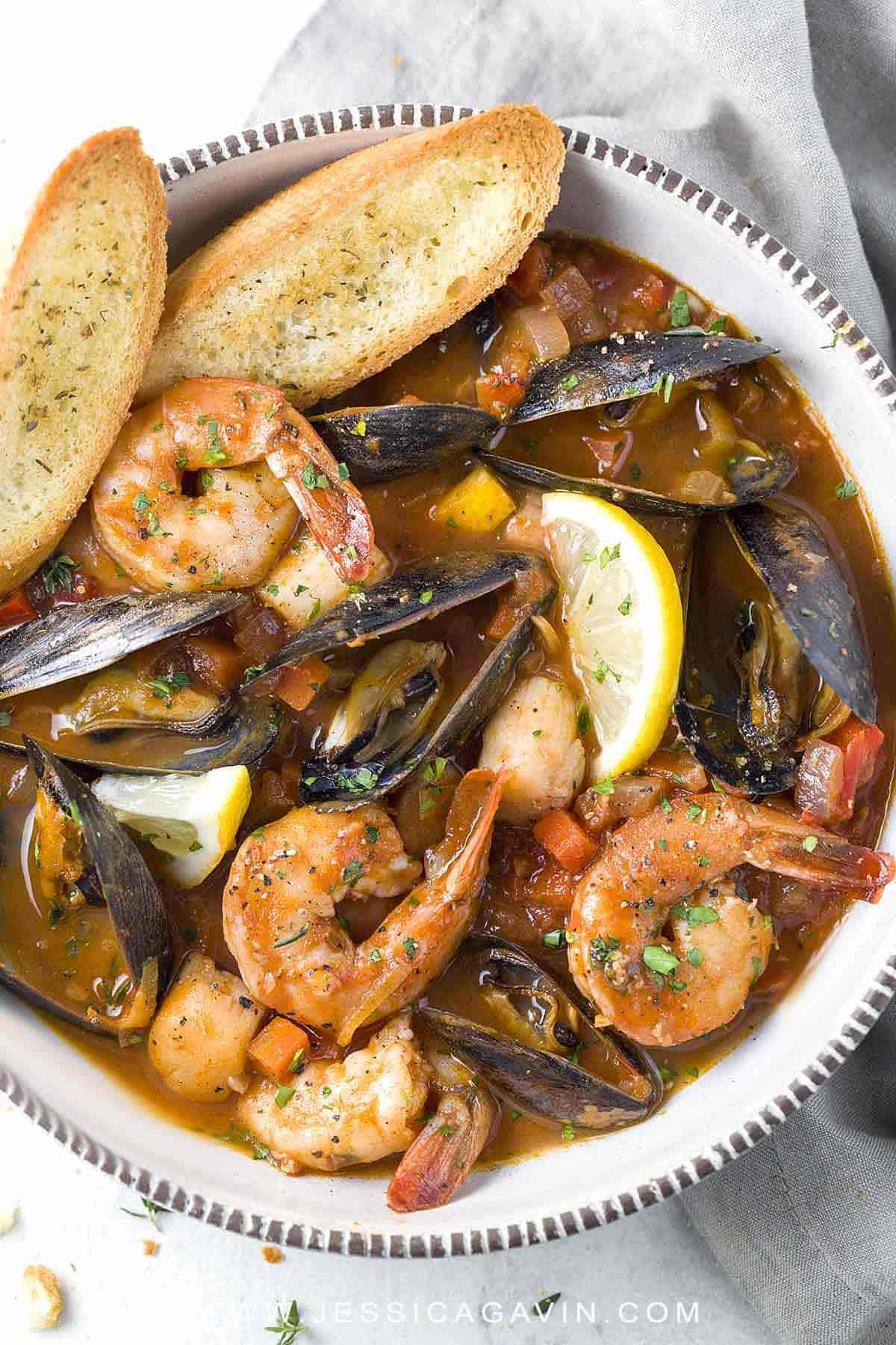 San Francisco Style Seafood Cioppino - A pot of fresh mussels, shrimp, and scallops simmered in a savory tomato and red wine broth. Served with homemade crunchy croutons! #seafoodstew #cioppino #bayareacuisine
