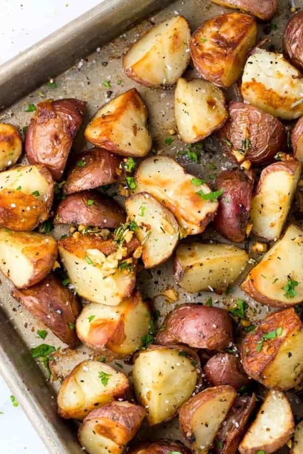 Crispy garlic roasted potatoes seasoned with rosemary on a baking sheet