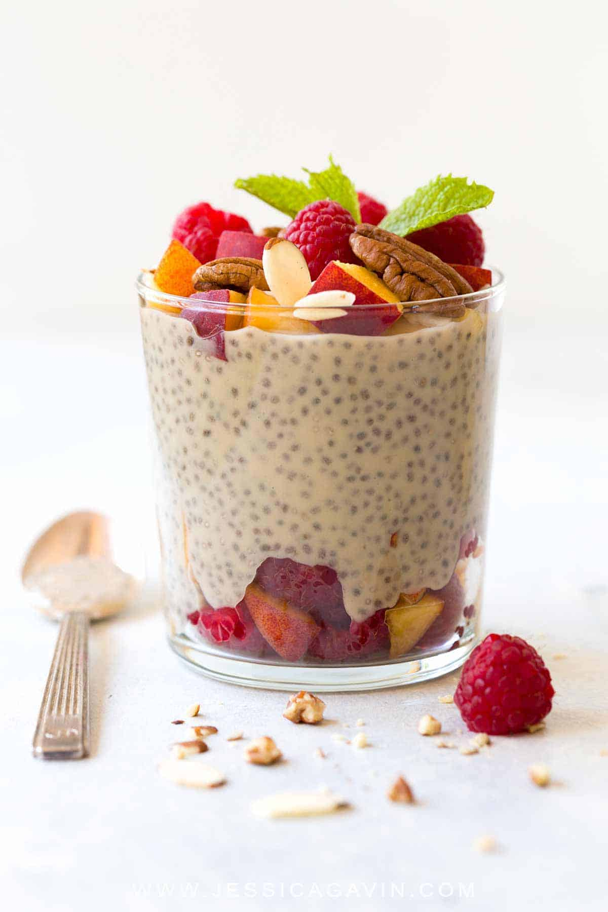 Chia seed protein pudding combines healthy nutrients like fiber and probiotics in every cup. Made with only 3 ingredients for an easy make-ahead recipe! Topped with fresh peaches, raspberries, and nuts for a tasty vegan snack. #chiaseeds #pudding #breakfast #vegan