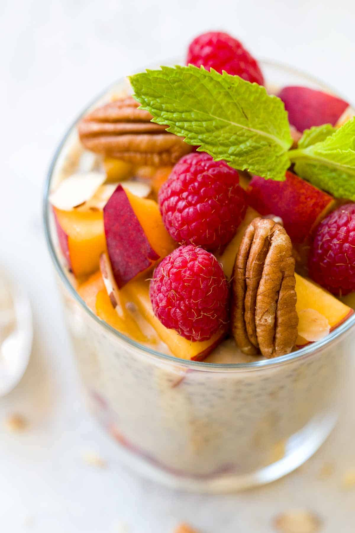 Glass cup of chia seed pudding with raspberries, chopped peaches, and walnuts on top