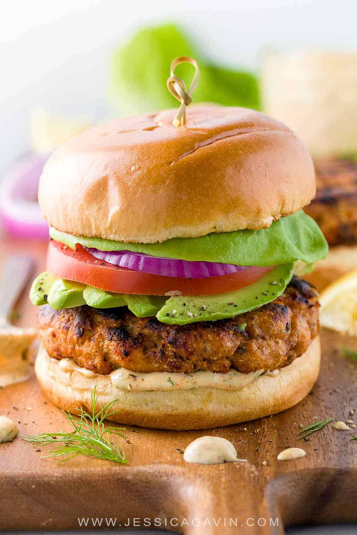 Salmon burgers with lemon dill sauce take the seafood sandwich to the next level. Healthy protein grilled to perfection and topped with lettuce, tomato, onions, and avocado. #salmonburger #bbq #salmonrecipes #burger #fishburger