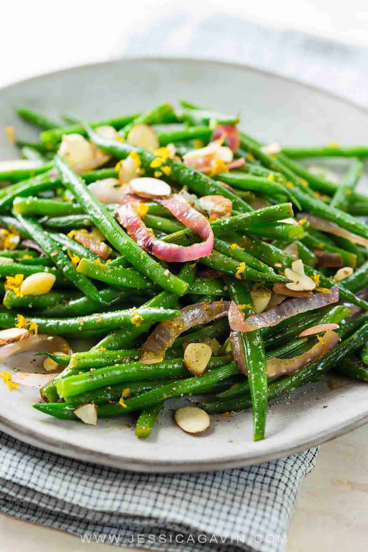 Green beans with almonds are a fast and healthy side dish. Sautéed with garlic, onions and orange juice, topped with crunchy nuts. #greenbeans #sidedish #lowcarb #vegan