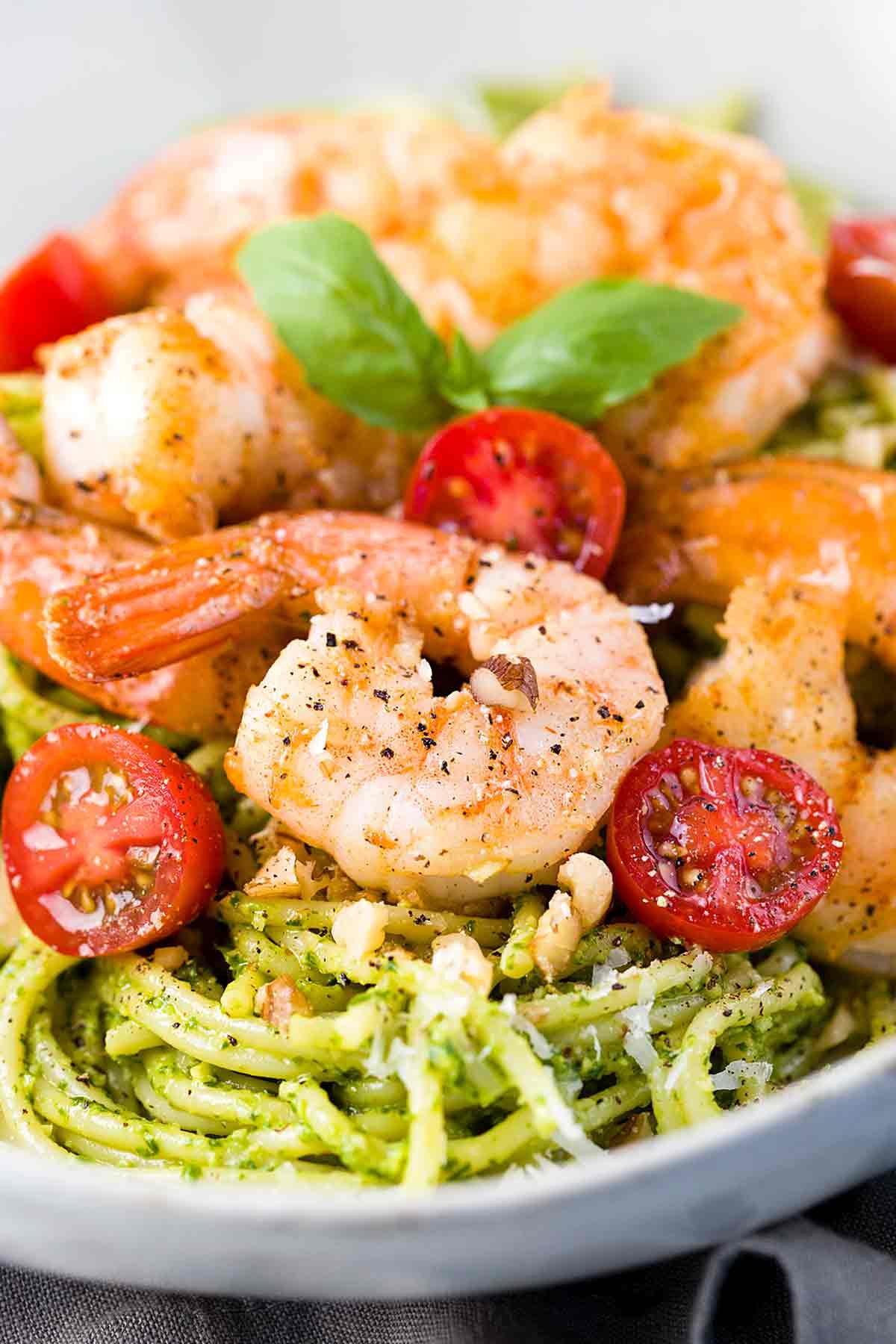White bowl with pesto shrimp pasta and cherry tomatoes