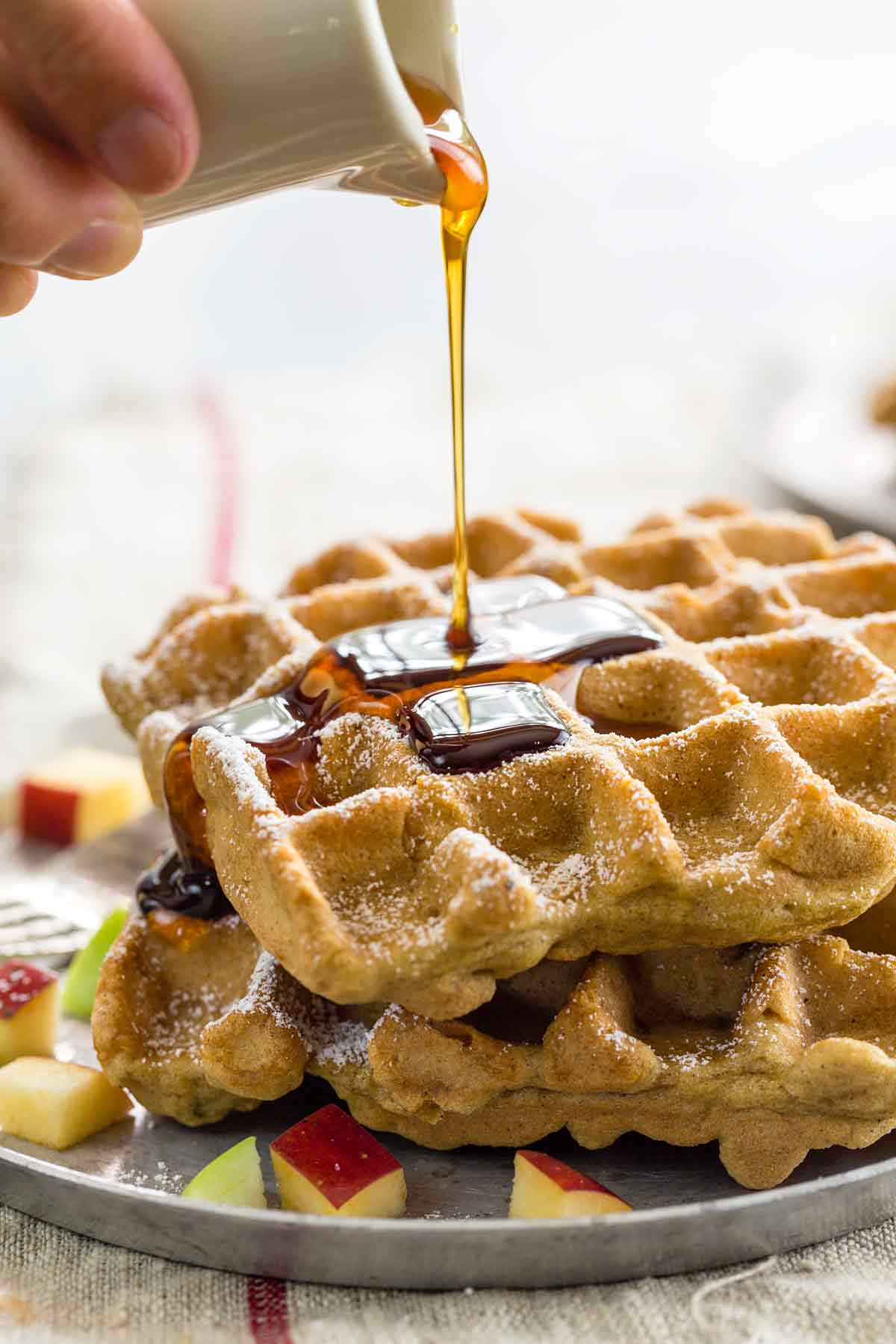 Maple syrup being poured over a stack of gluten free apple cinnamon waffles
