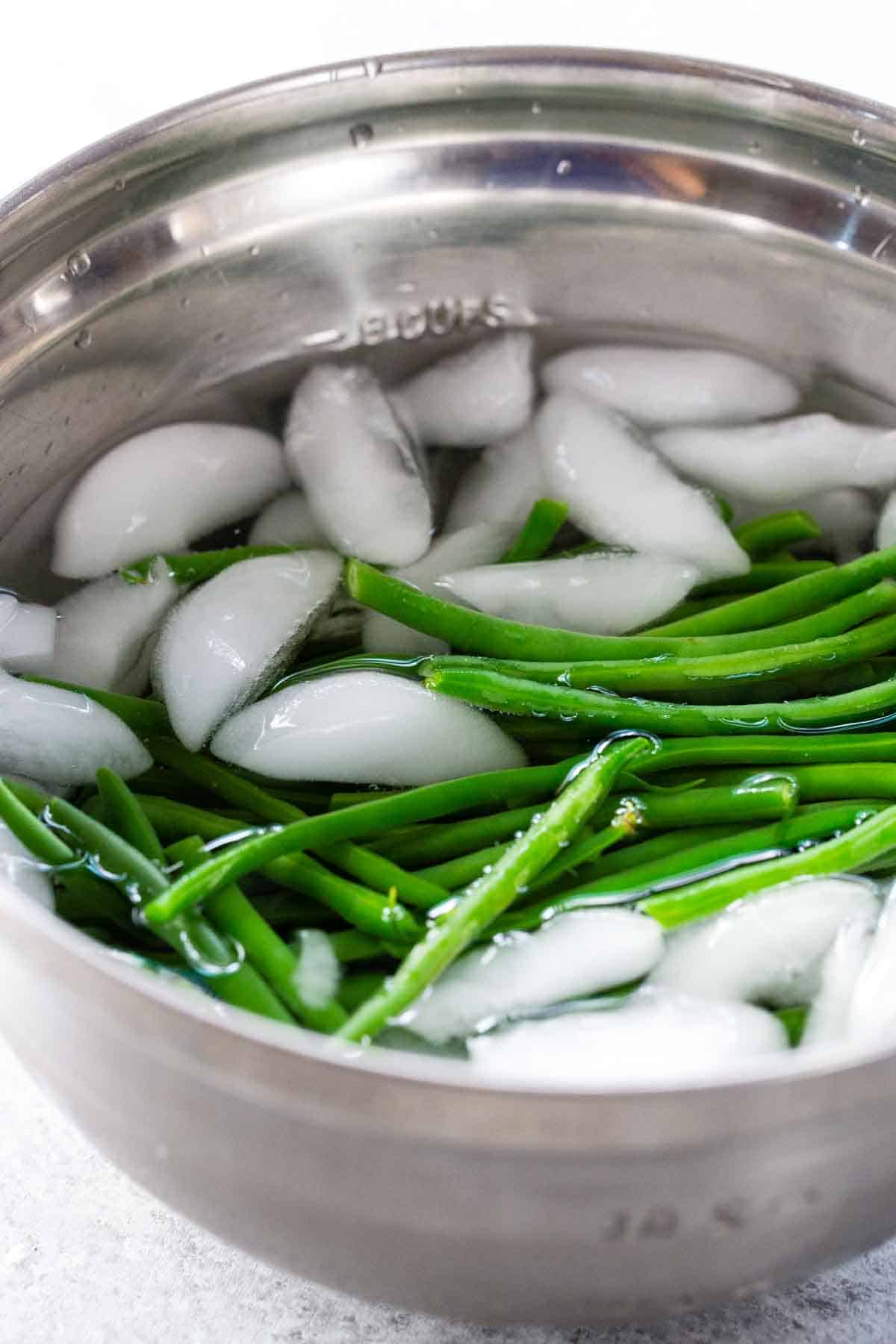Large silver bowl of green beans and ice cubes