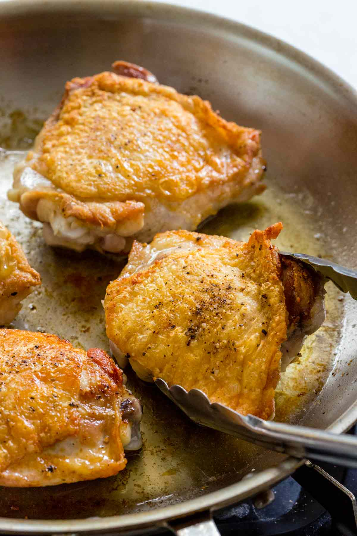 chicken thighs with crispy skin in a saute pan