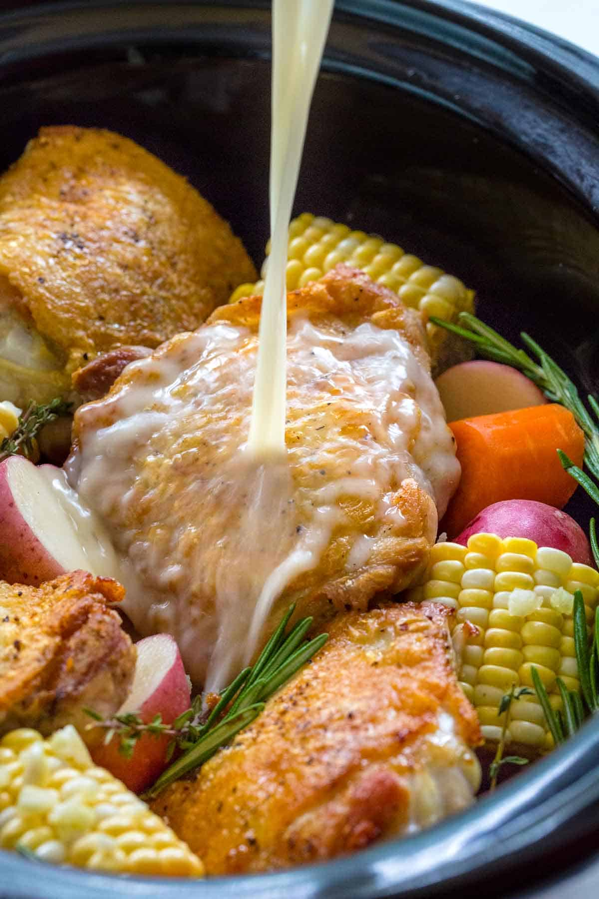 lemon sauce being poured over top chicken that is inside a slow cooker
