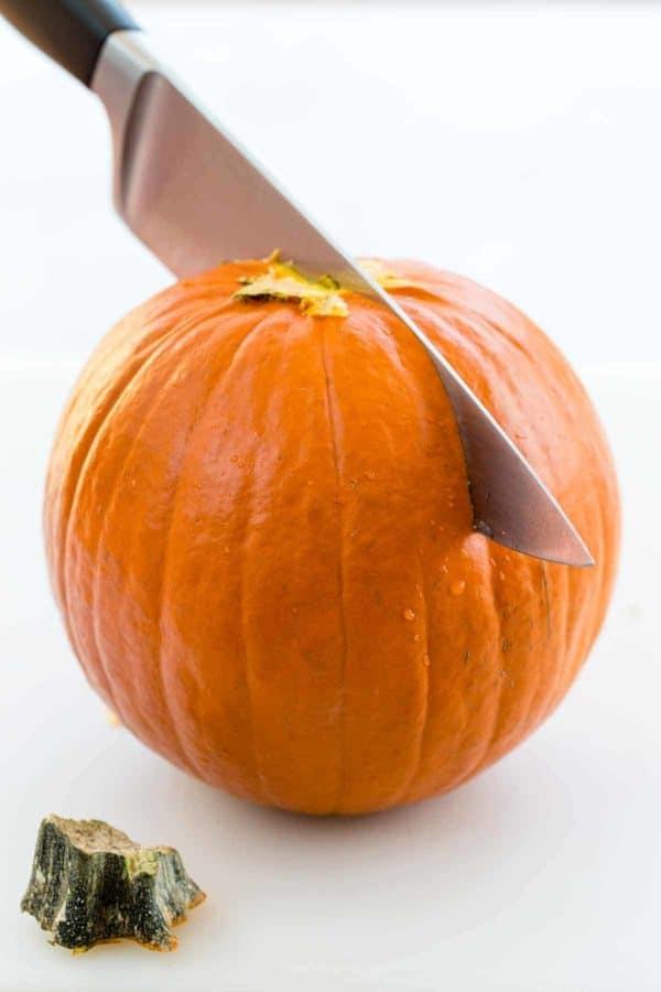 Orange Pumpkin with knife blade half way through