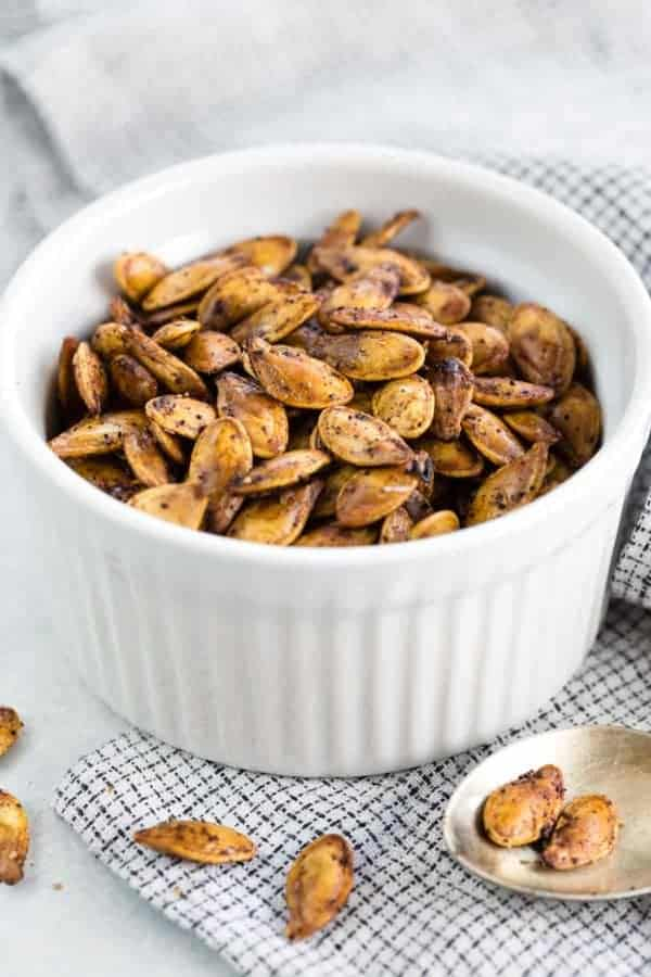 A white ramekin holding oven roasted pumpkin seeds