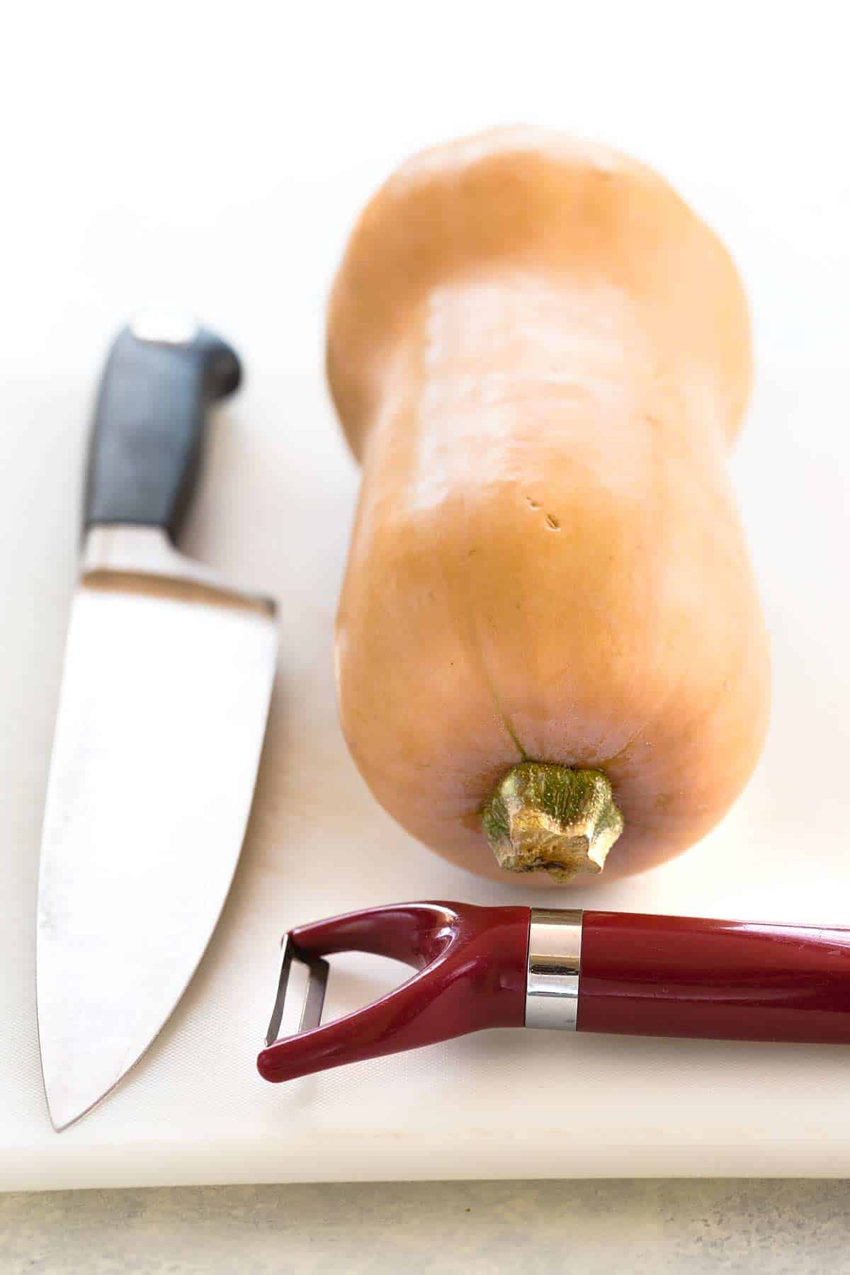 Cutting board with chef knife, peeler, and an uncut butternut squash