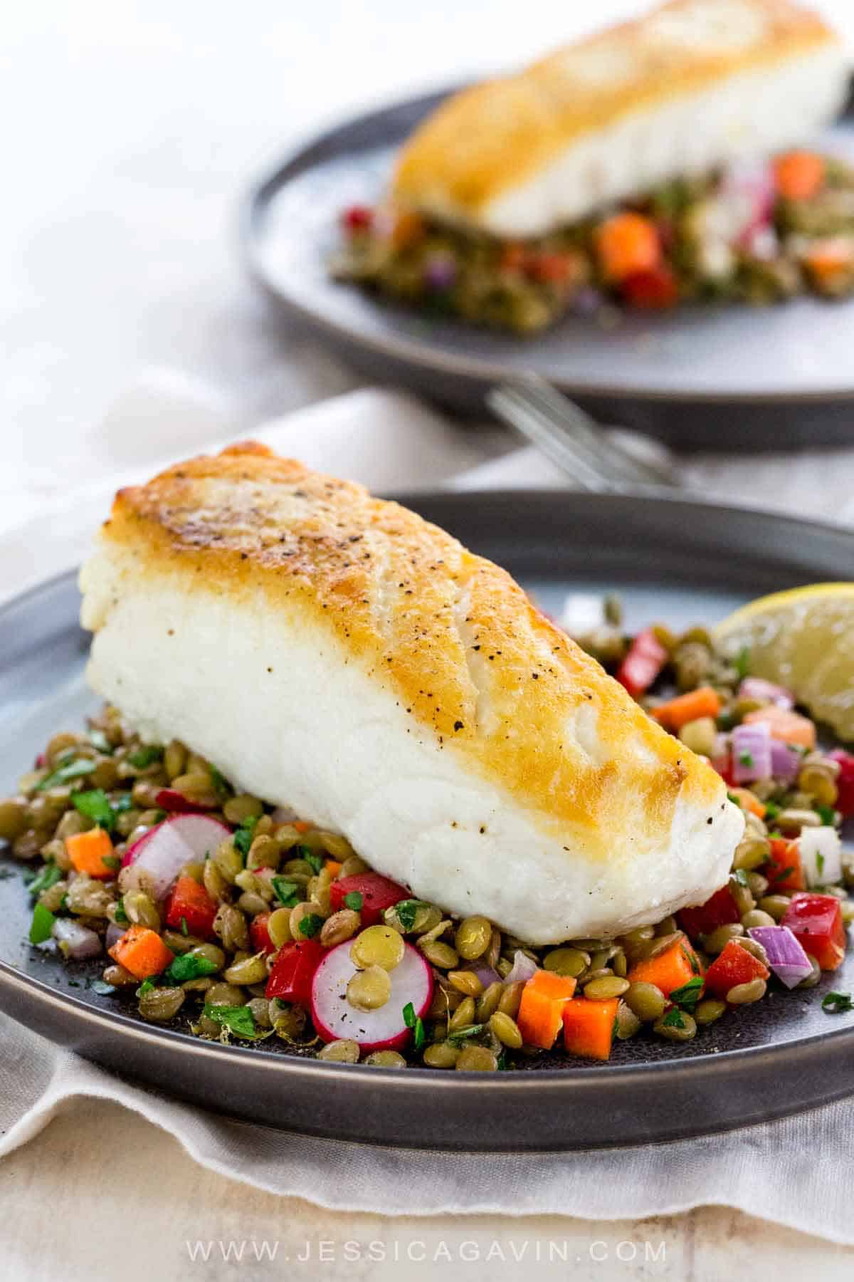 Pan-roasted halibut with a golden sear and served with a white wine braised lentil vegetable salad that is tossed with a lemon basil dressing. #halibut #datenight #fish #cooking