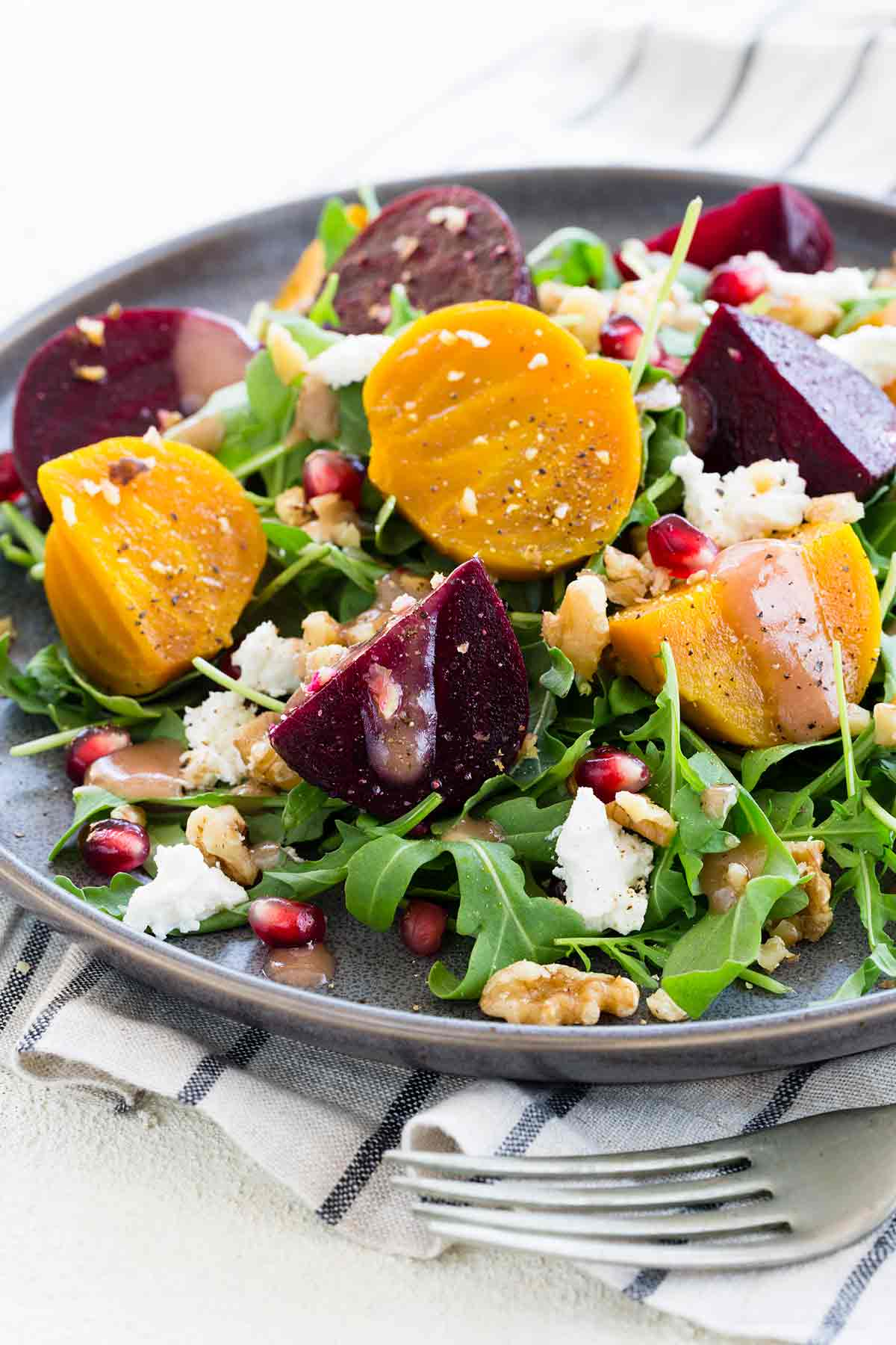 Sliced golden beets and purple beets on top of a green salad