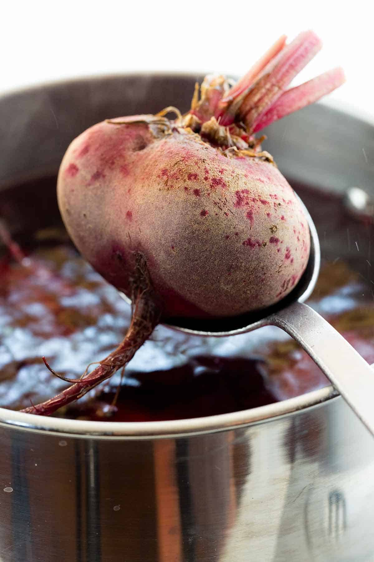 Spoon lowering a beet into boiling water