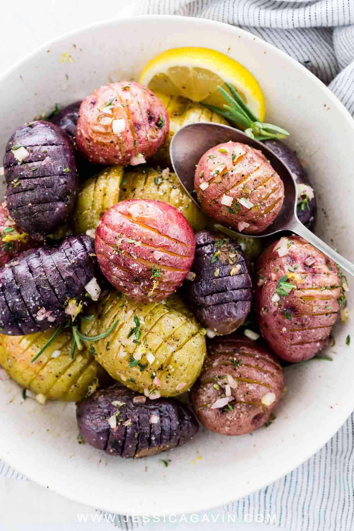 Hasselback potatoes roasted until crisp and topped with a tangy lemon garlic sauce. A flavorful and wholesome side dish bursting with fresh herbs and seasonings. #sidedish #potatoes #hasselback #vegan #whole30