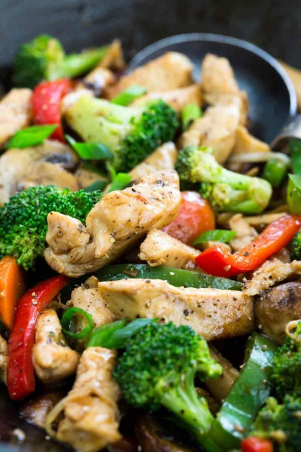 Chicken, broccoli and bell peppers being sautéed in a wok