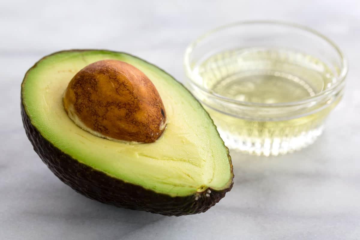 Cut open avocado and avocado oil in glass