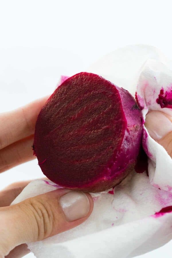 Wiping the skin off a beet with paper towel