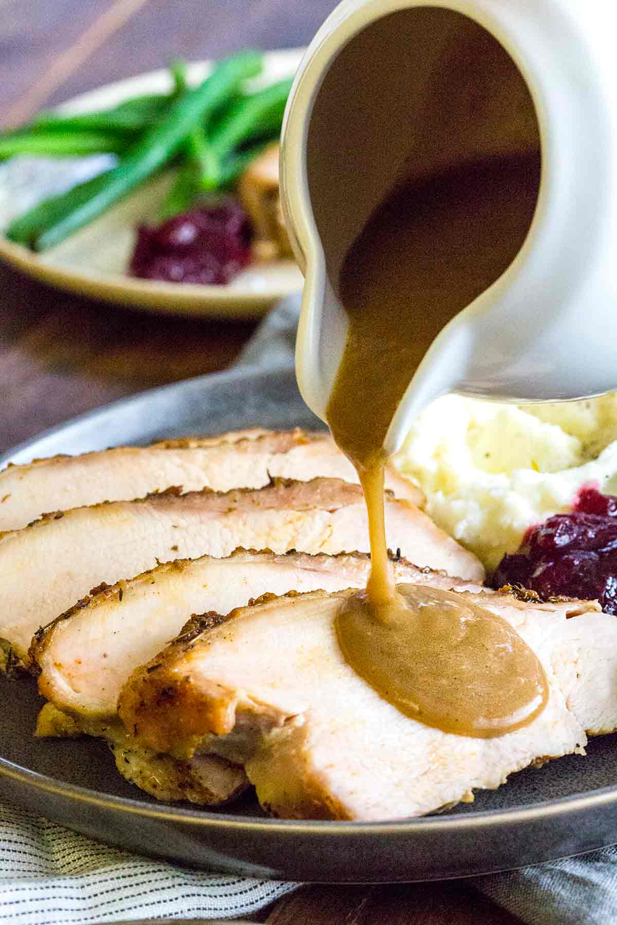 Pouring gravy over slices of turkey on a plate