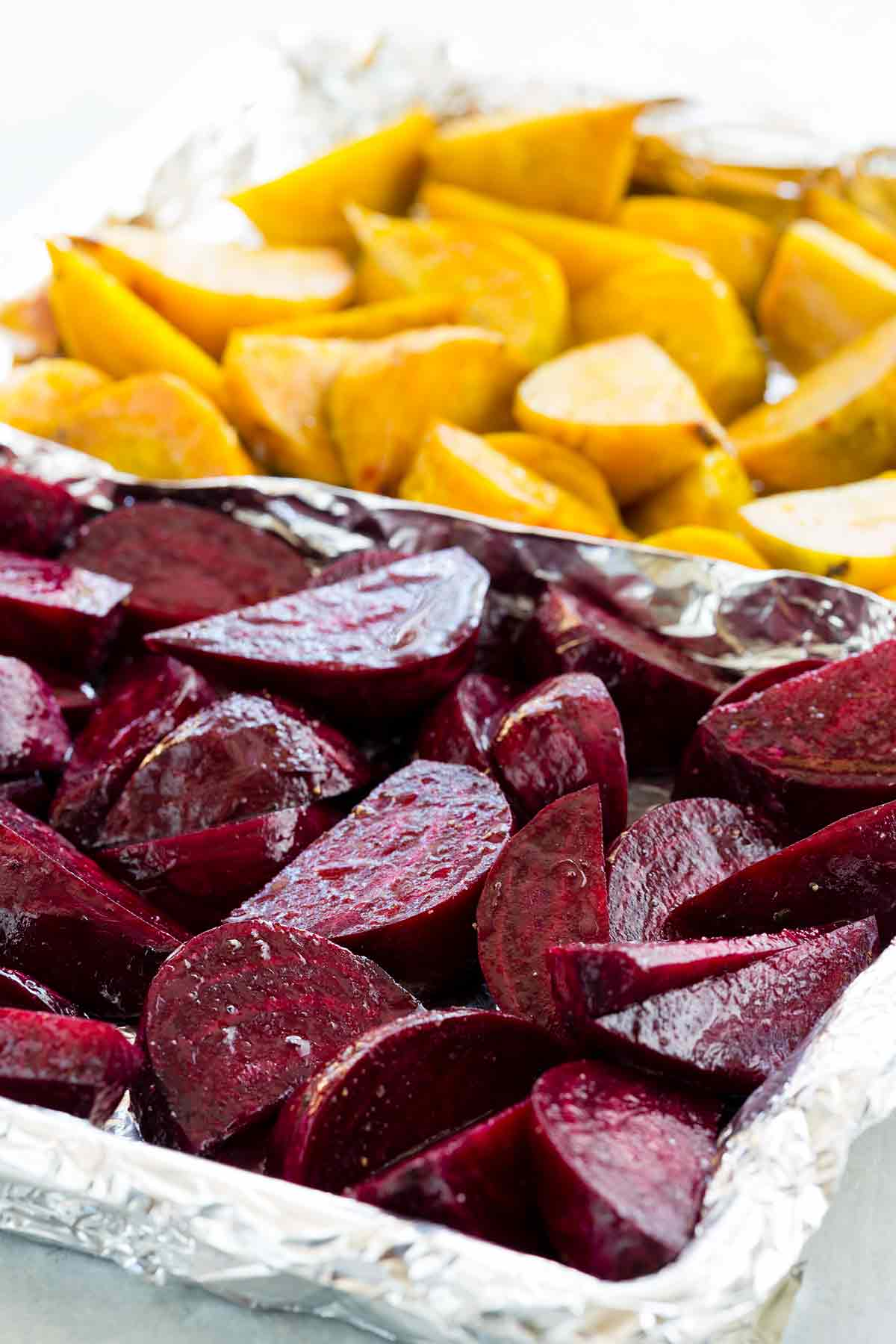 Sliced purple and gold beets on a roasting pan