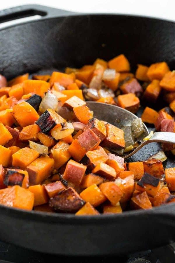 Metal spoon mixing diced sweet potato in a cast iron pan