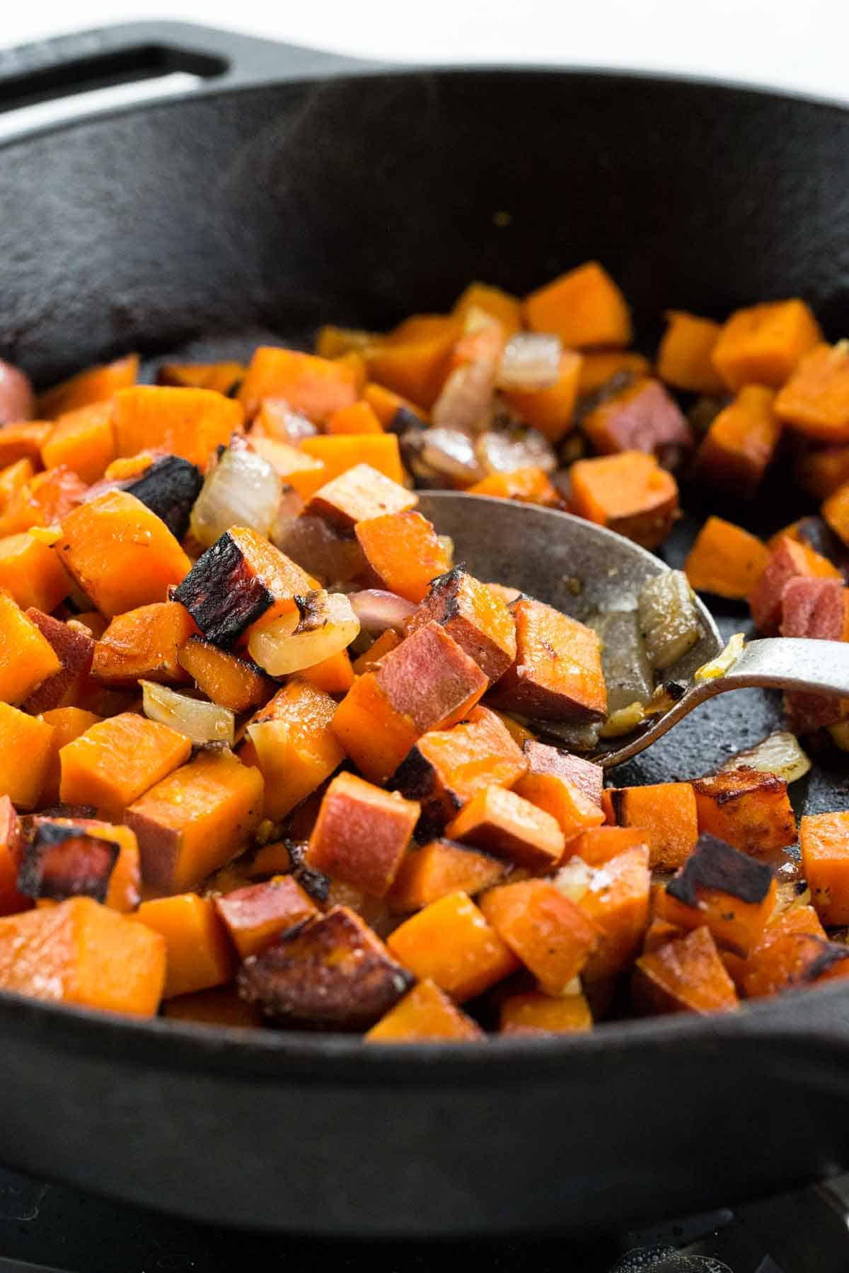 Metal spoon mixing diced sweet potato in a cast iron pan