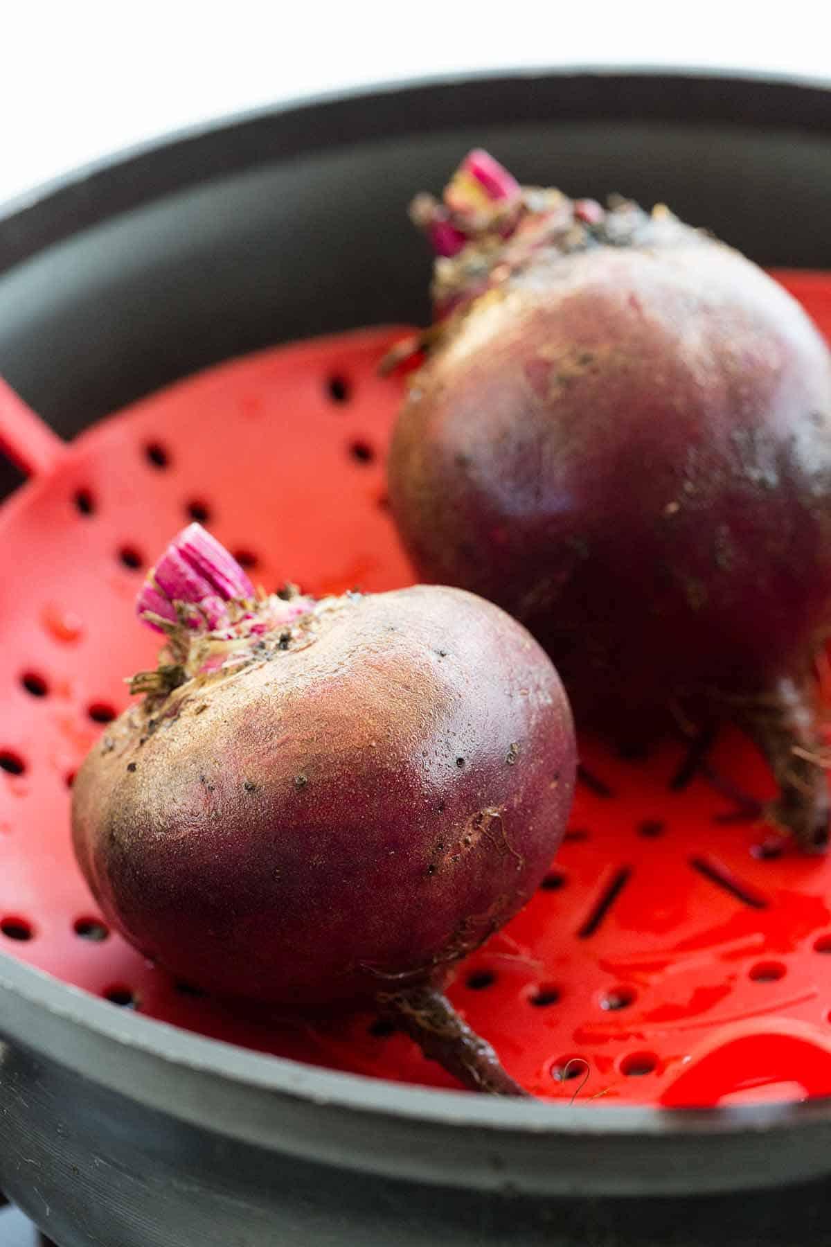 Two beets in a steamer basket