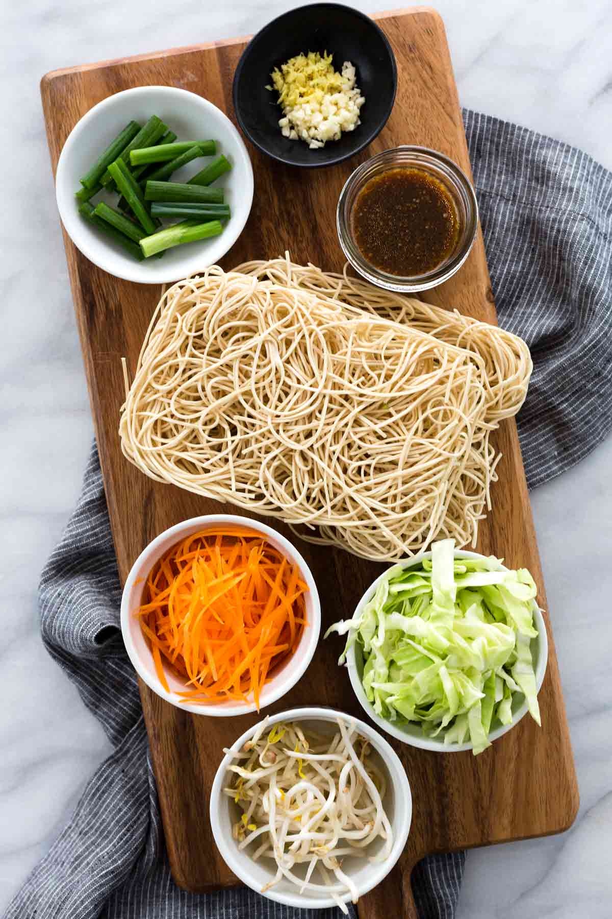 Pre-portioned chow mein ingredients on a wooden board